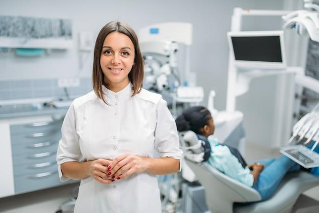 Sorrindo dentista feminina, clínica dentária, paciente na cadeira no fundo. mulher no gabinete de odontologia, estomatologia, tratamento dentário