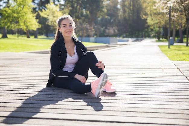 Sorrindo desportiva senhora relaxante no parque da cidade