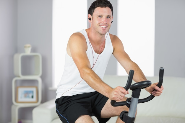 Sorrindo desportivo homem exercitar na bicicleta e ouvir música