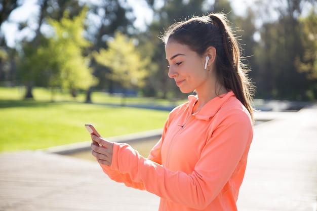 Sorrindo, desportivo, mulher, usando, smartphone, parque