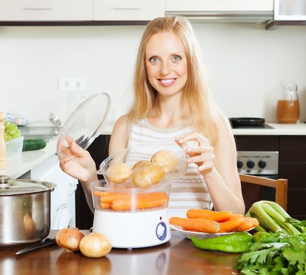 Sorrindo dona de casa batendo batatas com vaporizador elétrico
