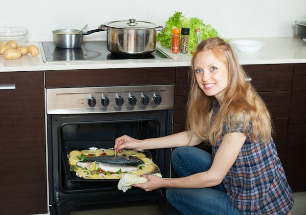 Sorrindo, dona de casa, cozinhar, água salgada, peixe, batatas, folha, panela
