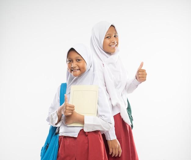 Sorrindo, duas garotas com véu vestindo uniformes do ensino fundamental com polegares para cima carregando mochilas e um ...