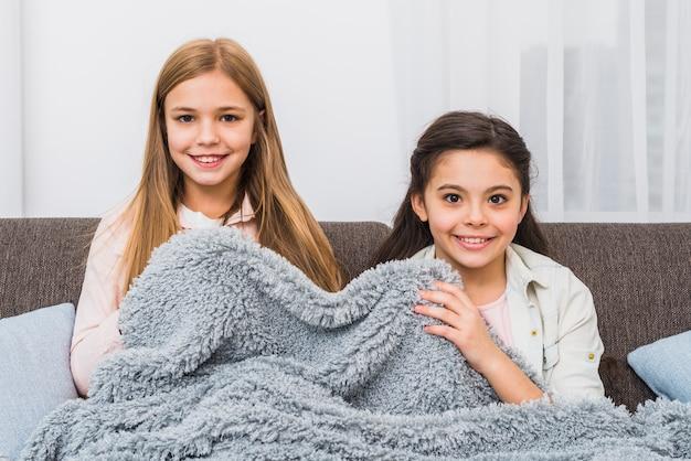 Sorrindo, duas meninas, sentando, ligado, sofá, cobertura, com, cinzento, cobertor