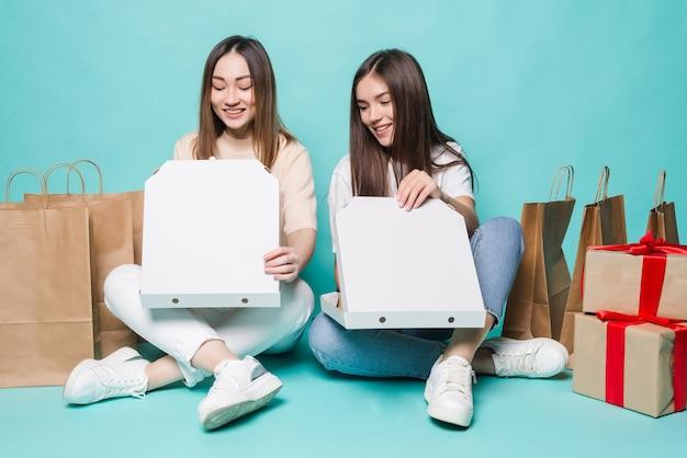 Sorrindo, duas meninas sentando sacolas de compras no chão e pizza aberta de presente na parede turquesa.