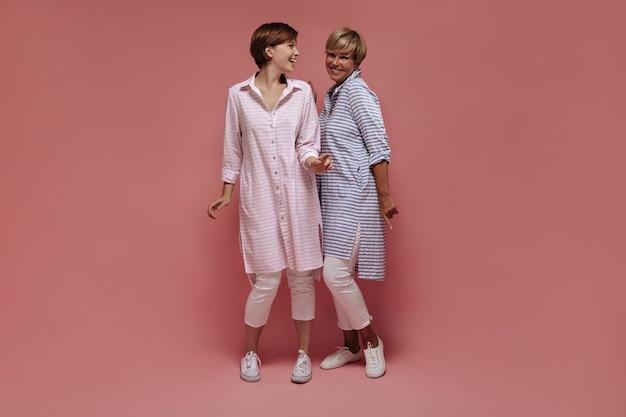 Sorrindo, duas mulheres de bom humor com cabelo curto, em camisas legais listradas e calças brancas dançando no fundo rosa isolado.
