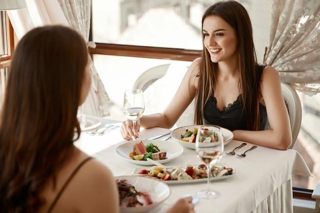 Sorrindo, duas mulheres jantam com vinho branco no elegante restaurante e conversam