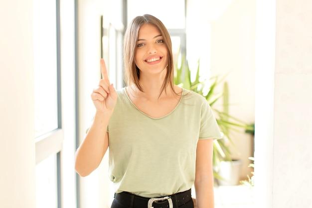 Sorrindo e a mulher parecendo amigável, mostrando o número um ou primeiro com a mão para a frente, em contagem regressiva