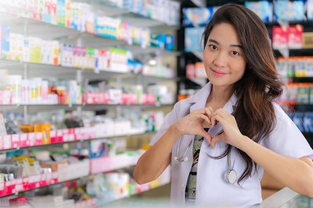 Sorrindo e feliz do farmacêutico feminino asiático mostrando o gesto de coração com as duas mãos na farmácia