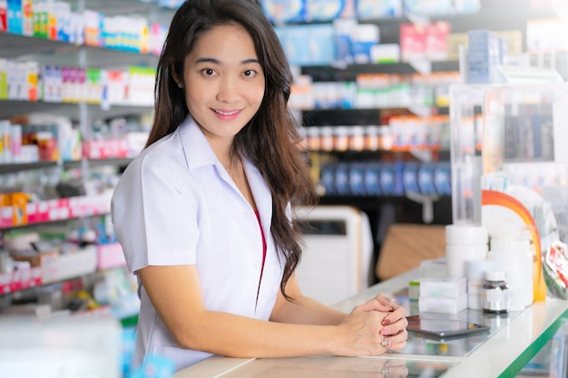 Sorrindo e feliz do farmacêutico feminino asiático na farmácia
