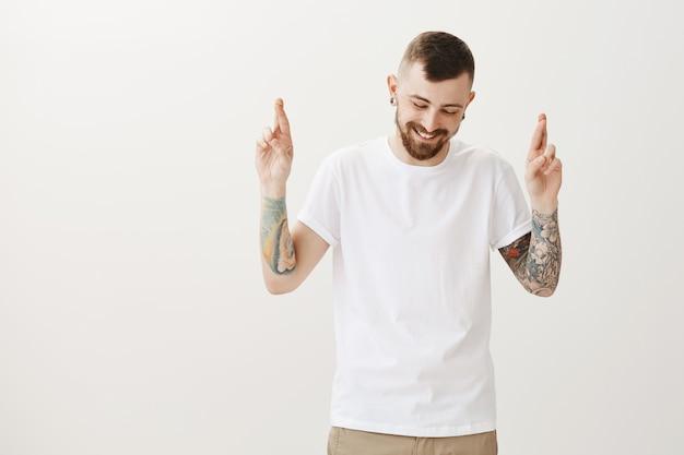 Sorrindo e feliz hipster cruzando os dedos boa sorte, desejando ou implorando