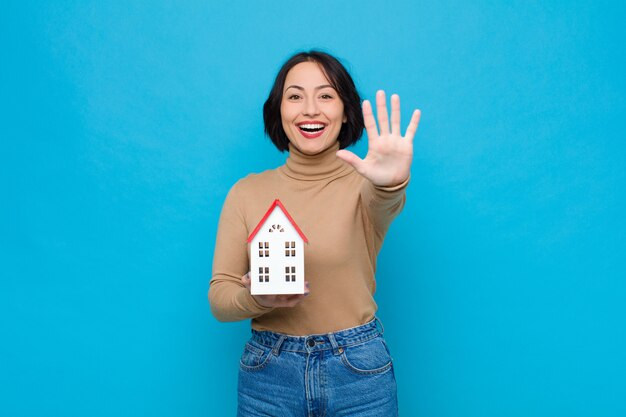Sorrindo e parecendo amigável, mostrando o número cinco ou quinto com a mão para a frente, contando