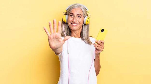 Sorrindo e parecendo amigável, mostrando o número cinco ou quinto com a mão para a frente, em contagem regressiva com fones de ouvido