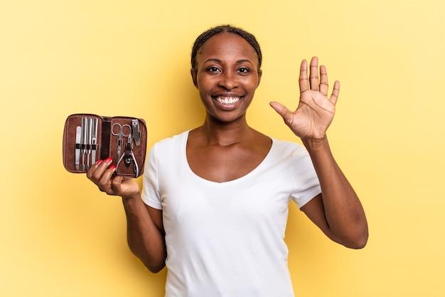 Sorrindo e parecendo amigável, mostrando o número cinco ou quinto com a mão para a frente, em contagem regressiva. conceito de ferramentas de unhas