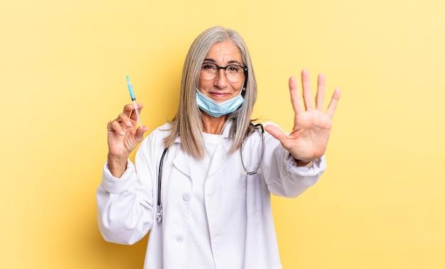 Sorrindo e parecendo amigável, mostrando o número cinco ou quinto com a mão para a frente, em contagem regressiva. conceito médico e vacina
