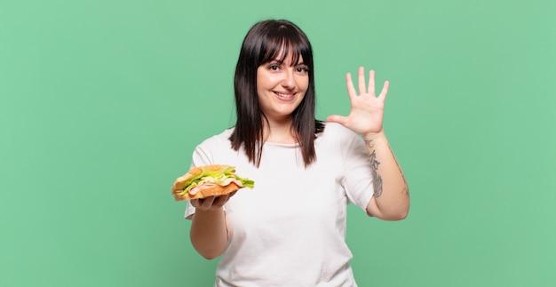 Sorrindo e parecendo amigável, mostrando o número cinco ou quinto com a mão para a frente, em contagem regressiva