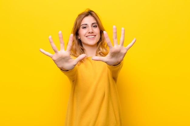 Sorrindo e parecendo amigável, mostrando o número dez ou décimo com a mão para a frente, contando