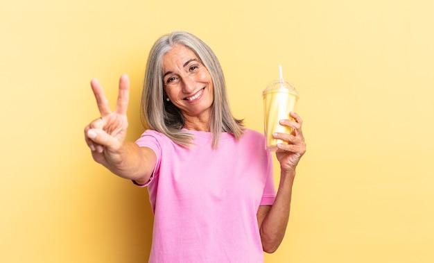 Sorrindo e parecendo amigável, mostrando o número dois ou o segundo com a mão para a frente, contando e segurando um milkshake