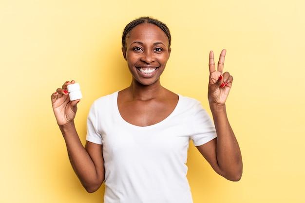 Sorrindo e parecendo amigável, mostrando o número dois ou o segundo com a mão para a frente, em contagem regressiva. conceito de pílulas