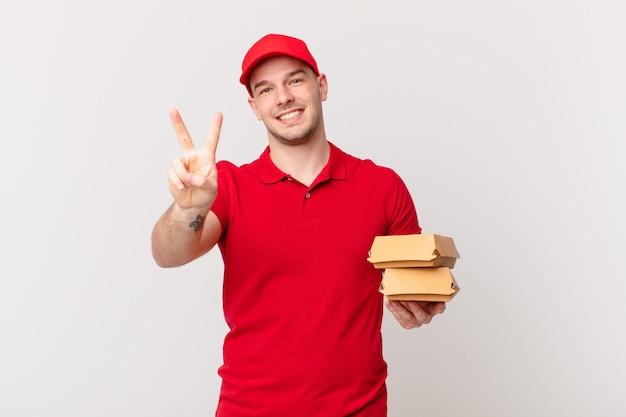 Sorrindo e parecendo amigável, mostrando o número dois ou o segundo com a mão para a frente, em contagem regressiva