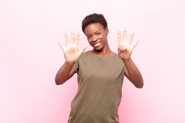 Sorrindo e parecendo amigável, mostrando o número nove ou nono com a mão para a frente, contando