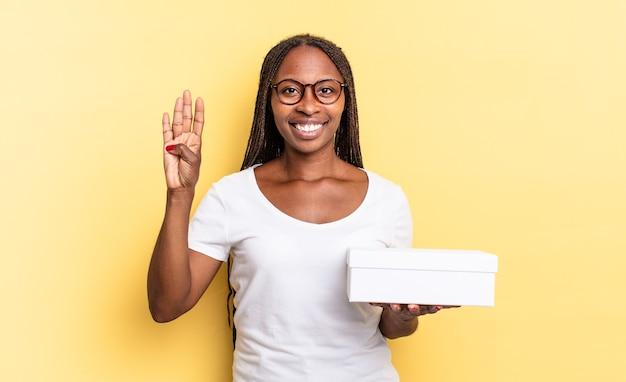 Sorrindo e parecendo amigável, mostrando o número quatro ou o quarto com a mão para a frente, contando e segurando uma caixa vazia