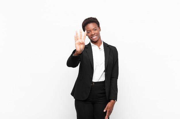 Sorrindo e parecendo amigável, mostrando o número quatro ou quarto com a mão para a frente, contando