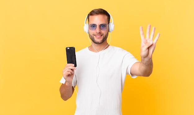 Sorrindo e parecendo amigável, mostrando o número quatro, ouvindo música com fones de ouvido e um smartphone