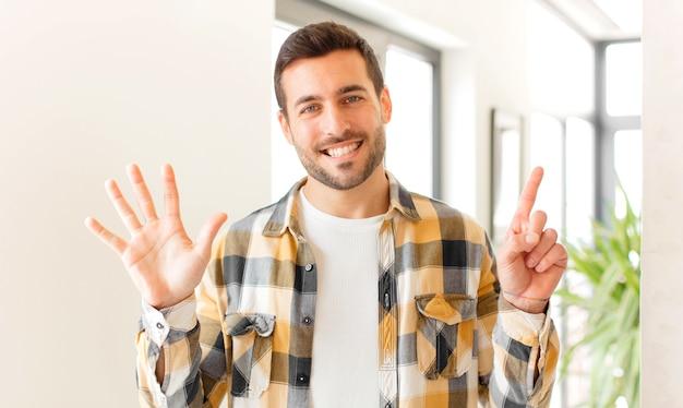 Sorrindo e parecendo amigável, mostrando o número seis ou sexto com a mão para a frente, em contagem regressiva