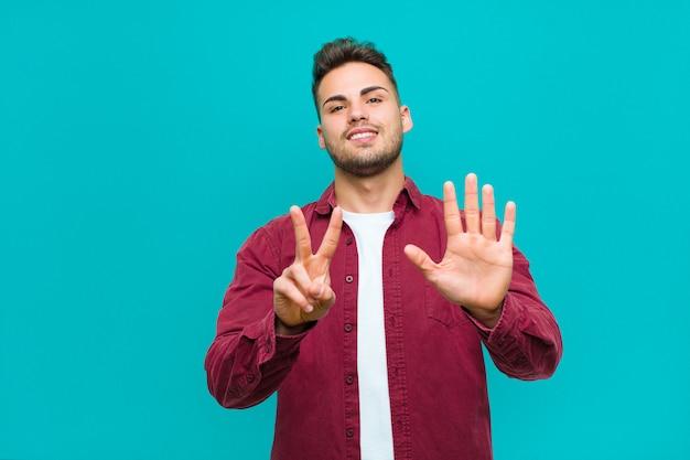 Sorrindo e parecendo amigável, mostrando o número sete ou sétimo com a mão para a frente, contando