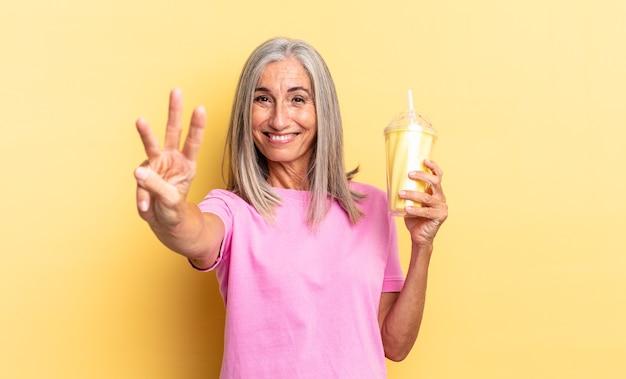 Sorrindo e parecendo amigável, mostrando o número três ou terceiro com a mão para a frente, contando e segurando um milkshake