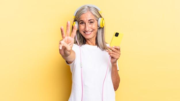 Sorrindo e parecendo amigável, mostrando o número três ou terceiro com a mão para a frente, em contagem regressiva com fones de ouvido
