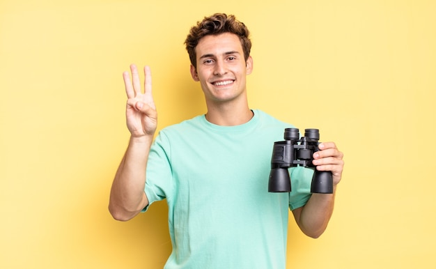 Sorrindo e parecendo amigável, mostrando o número três ou terceiro com a mão para a frente, em contagem regressiva. conceito de binóculos