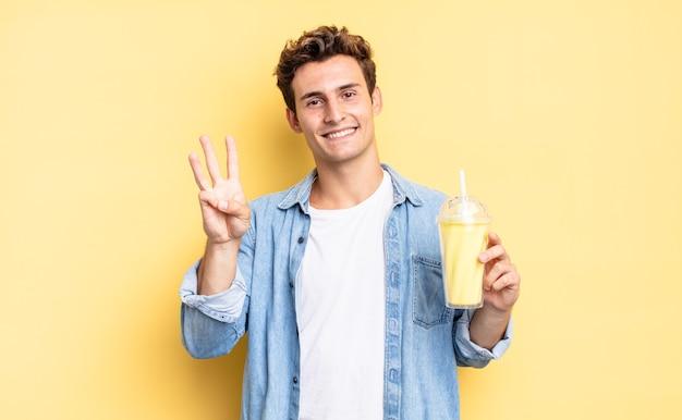 Sorrindo e parecendo amigável, mostrando o número três ou terceiro com a mão para a frente, em contagem regressiva. conceito de milkshake