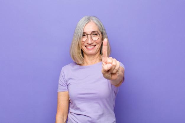 Sorrindo e parecendo amigável, mostrando o número um ou o primeiro com a mão para a frente, contando
