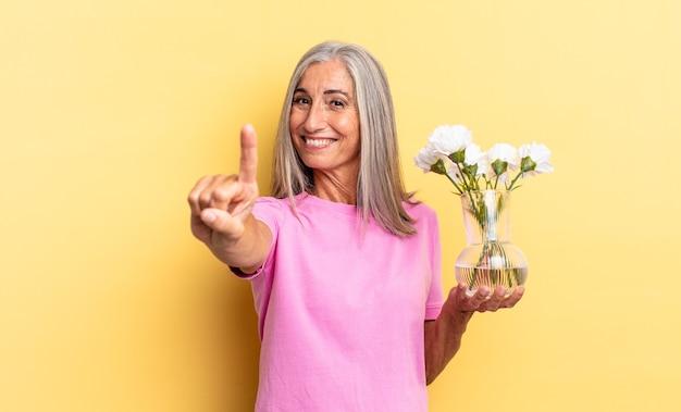 Sorrindo e parecendo amigável, mostrando o número um ou o primeiro com a mão para a frente, em contagem regressiva segurando flores decorativas