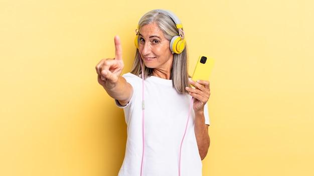 Sorrindo e parecendo amigável, mostrando o número um ou primeiro com a mão para a frente, em contagem regressiva com fones de ouvido