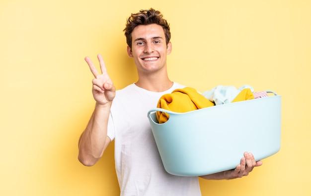 Sorrindo e parecendo feliz, despreocupado e positivo, gesticulando vitória ou paz com uma mão. conceito de lavagem de roupas
