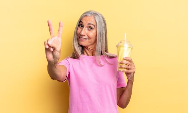 Sorrindo e parecendo feliz, despreocupado e positivo, gesticulando vitória ou paz com uma mão e segurando um milkshake