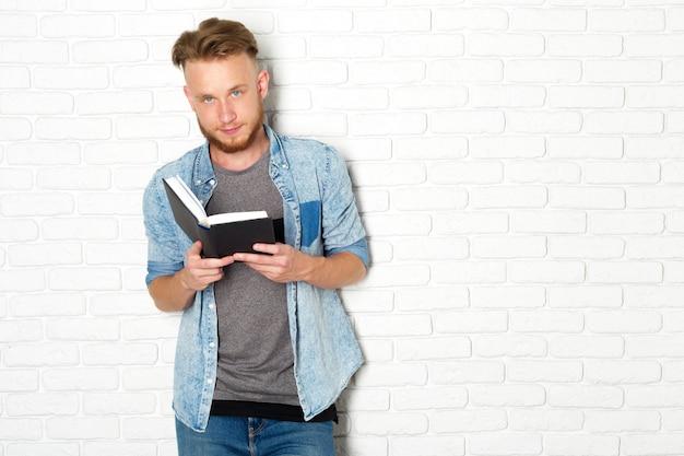 Sorrindo e pensativo casual homem lendo um livro