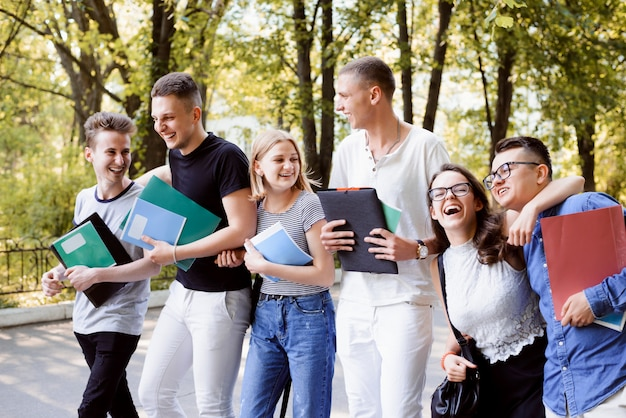 Sorrindo e rindo alunos andando no parque durante as férias, contando piadas