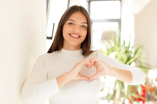 Sorrindo e se sentindo feliz fofo romântico e apaixonado fazendo formato de coração com as duas mãos