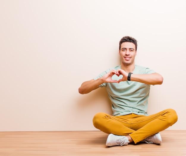 Sorrindo e se sentindo feliz, fofo, romântico e apaixonado, fazendo formato de coração com as duas mãos
