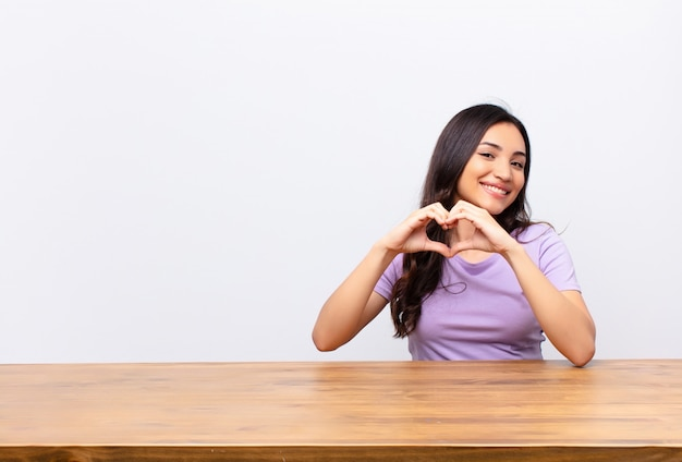 Sorrindo e sentindo-se feliz, fofo, romântico e apaixonado, fazendo formato de coração com as duas mãos