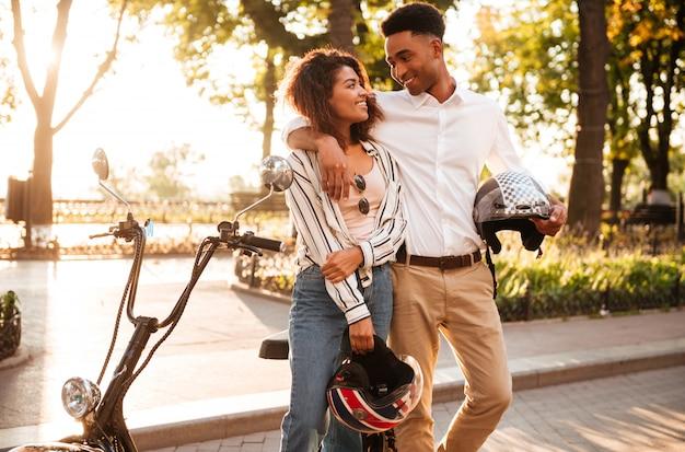 Sorrindo ee casal africano abraçando perto da moto moderna no parque