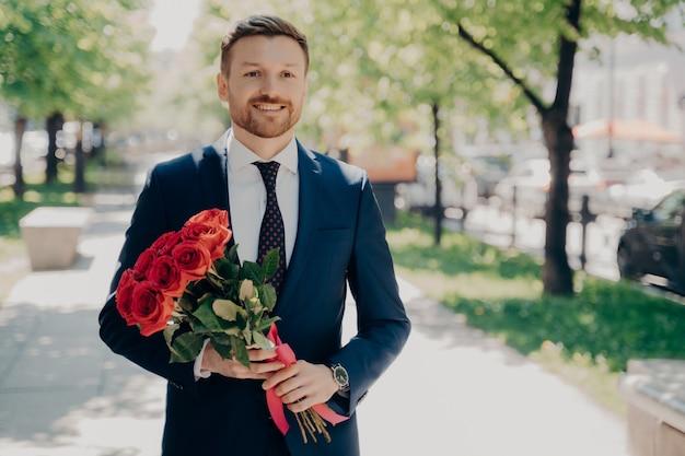 Sorrindo elegante cavalheiro barbudo em um smoking azul escuro com um grande buquê de rosas vermelhas caminhando ao longo do beco verde no parque em um dia ensolarado para encontrar sua amada. conceito de encontro romântico ao ar livre
