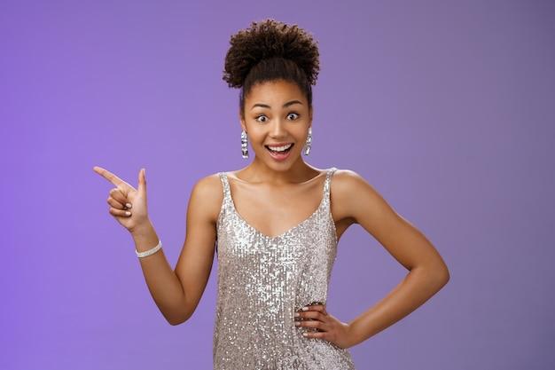 Sorrindo elegante garota afro-americana festa de formatura usando prata brilhante vestido de noite apontando o dedo indicador esquerdo arregalar os olhos surpreso impressionado receber oportunidade de vida, fundo azul.