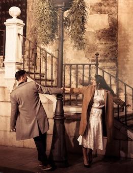 Sorrindo, elegante, mulher, e, homem jovem, girar, ao redor, abajur rua