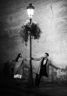 Sorrindo, elegante, mulher, e, homem jovem, whirling, perto, iluminado, abajur rua
