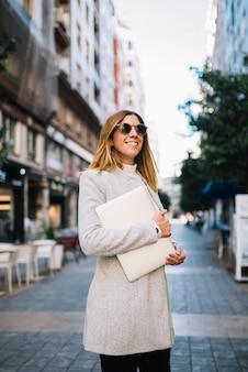 Sorrindo, elegante, mulher jovem, com, óculos de sol, e, laptop, ligado, rua, em, cidade